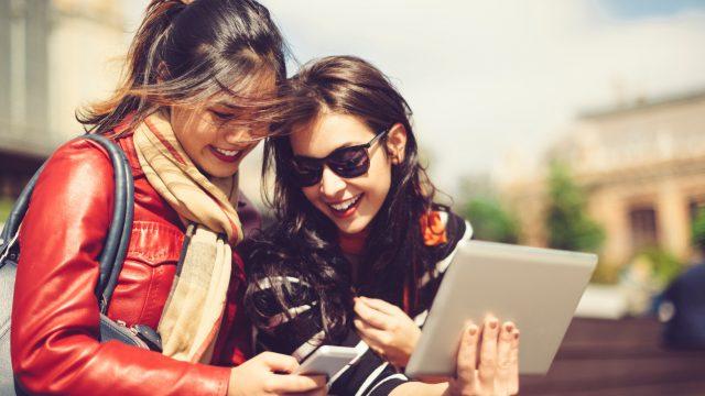 Junge Frauen zeigen sich gegenseitig ihre Bildersammlung