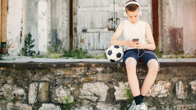 Ein Junge sitzt auf der Mauer und beschäftigt sich mit Facebook