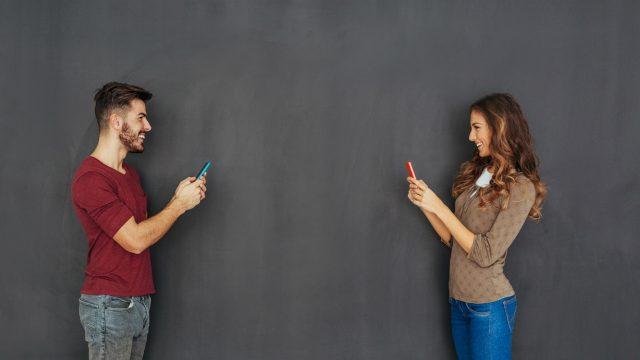 Mann und Frau chatten via Smartphone.