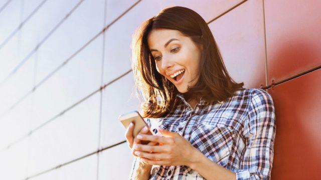 Frau mit Smartphone freut sich über Apps