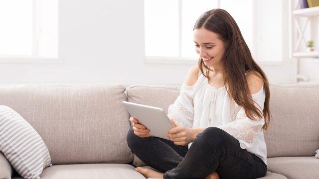 Junge Frau sitzt mit Tablet auf der Couch