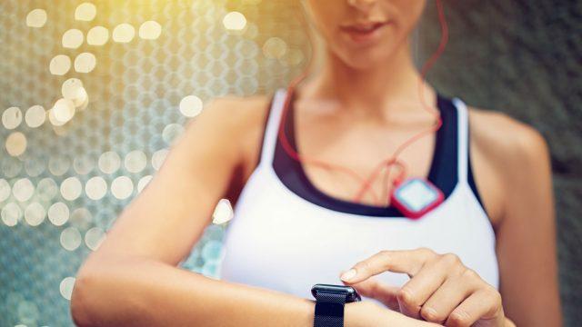 Frau nutzt während des Lauftrainings ihre Smartwatch.