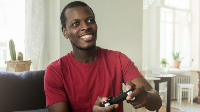Junger Mann zockt mit seinem PS4-Controller ein Nintendo Switch-Spiel.