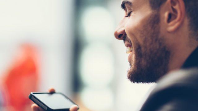 Ein junger Mann schaut sich ein Video auf seinem iPhone an