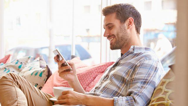 Junger Mann sitzt auf der Couch und schaltet die Akku-Warnung seines Smartphones aus.