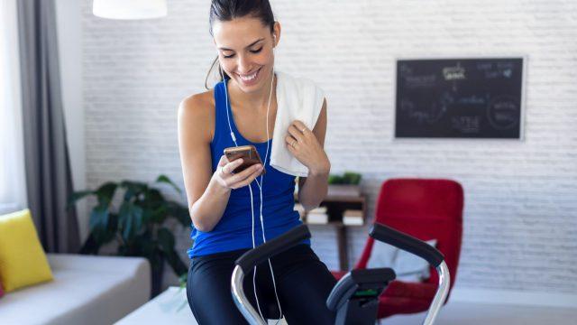 Frau nutzt Samsung Health am Handy, während sie Sport macht.