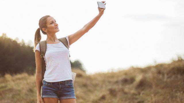 Eine junge Frau macht ein Selfie für ihr neues Facebook Profilbild