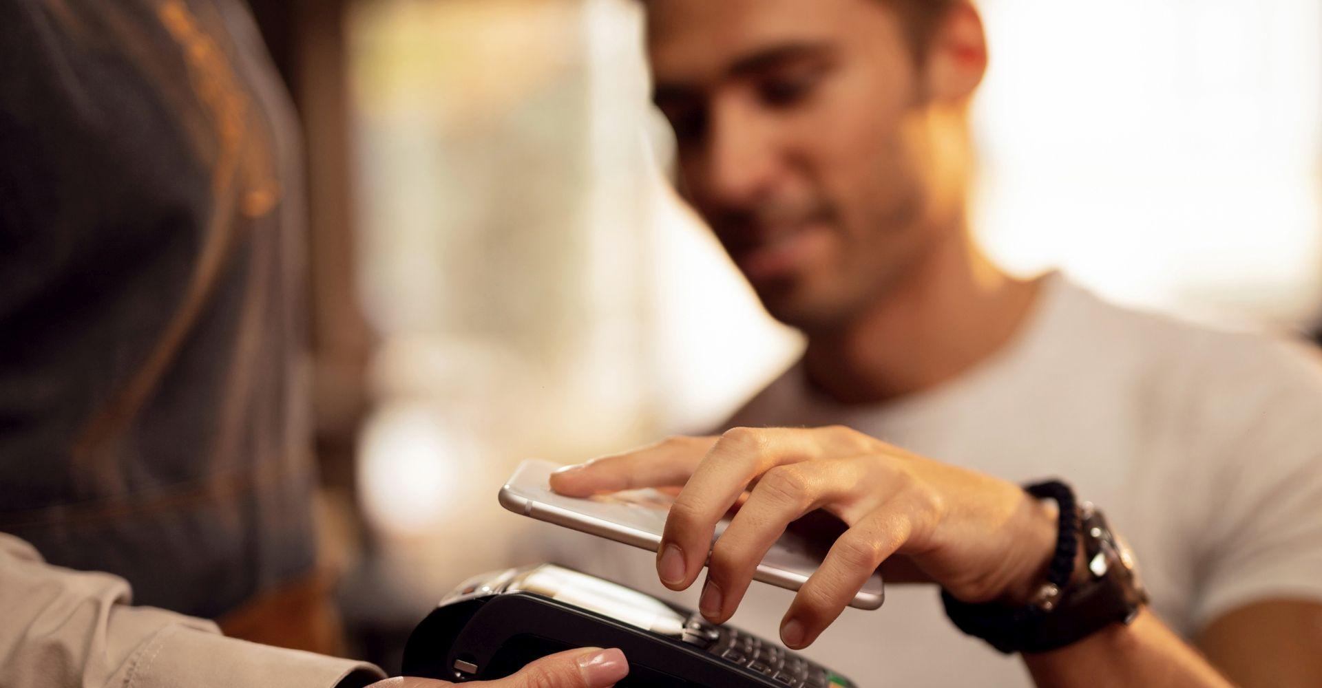 Mann bezahlt kontaktlos mit Smartphone.