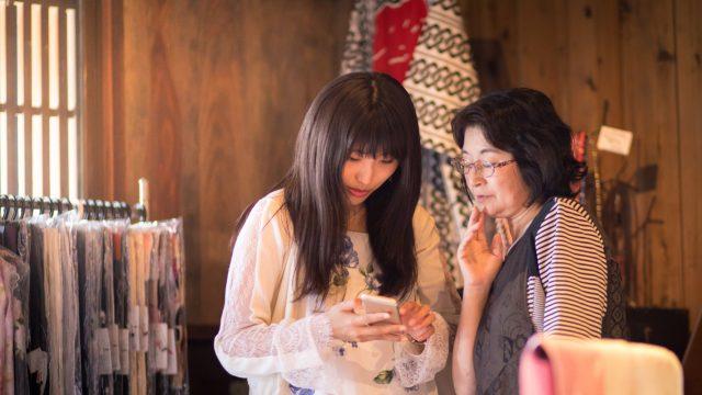 Zwei japanische Frauen schauen auf ein Smartphone