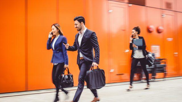 Junge Geschäftsleute checken ihre Termine im iOS-Kalender