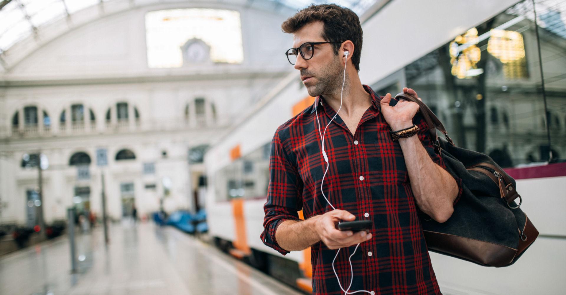 Junger Mann steuert seine Musik mit Google Maps am Smartphone und wartet auf den Zug.