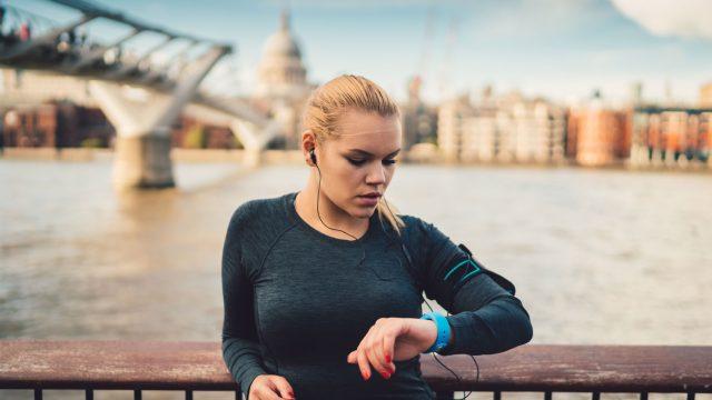 Frau mit Smartwatch beim Joggen am Wasser
