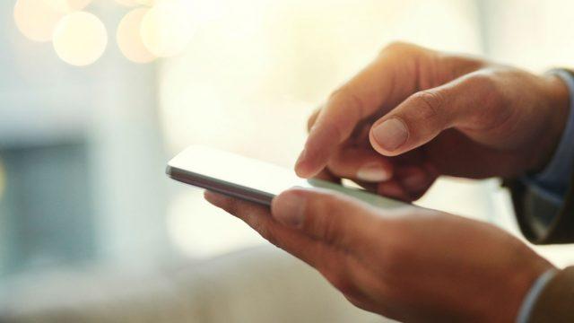 Junger Mann nutzt iOS 12 am iPhone.
