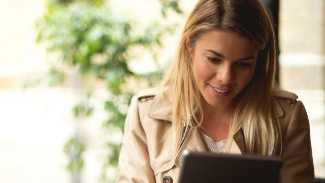 Junge Frau passt Apple Books beim Lesen auf dem Tablet an.