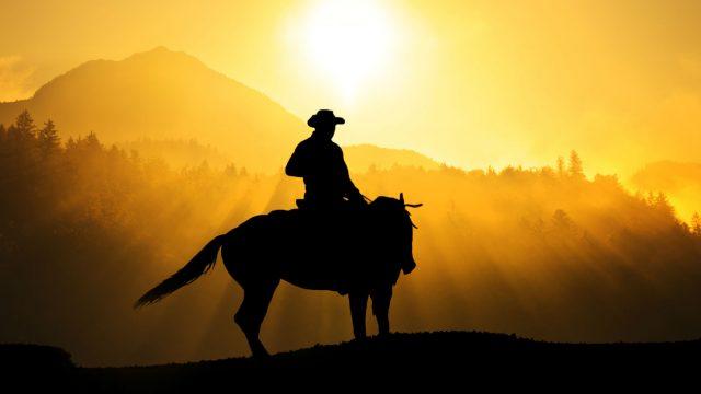 Junger Outlaw reitet auf dem Pferd durch den Wilden Westen.