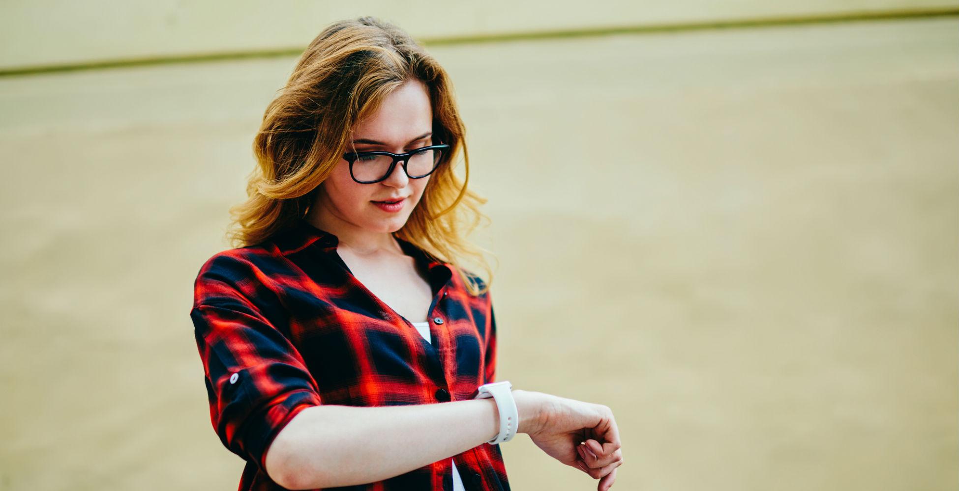 Junge Frau sieht auf ihre gereinigte Apple Watch.