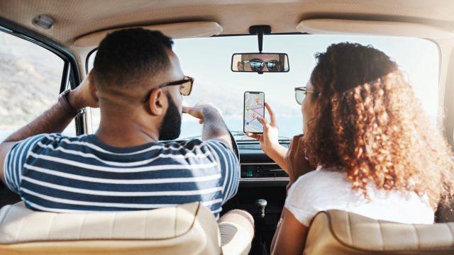 Paar nutzt im Auto eine Karten-App zur Navigation.