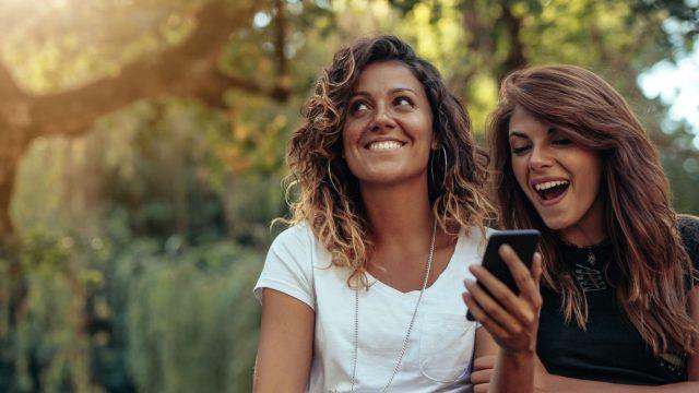 Freundinnen korrigieren am Smartphone die Gesichtserkennung der Fotos-App.