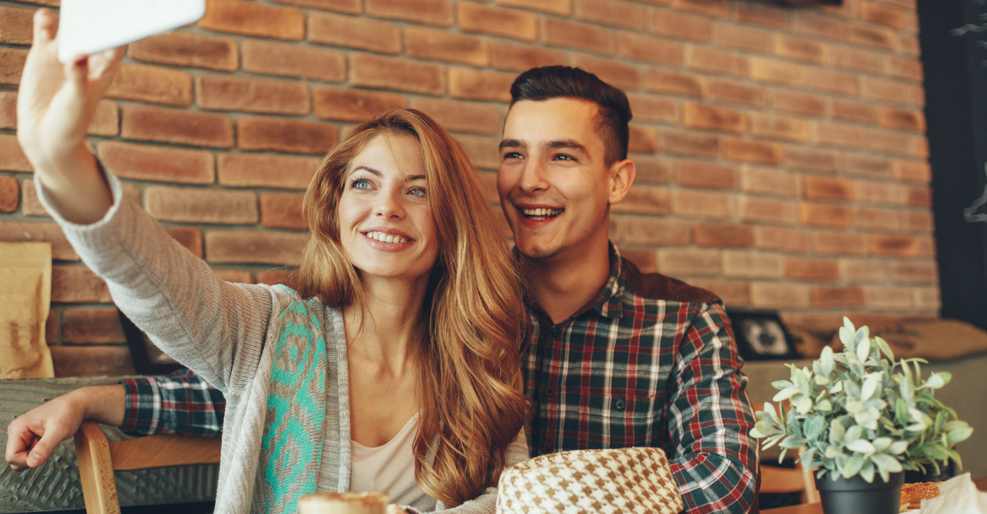 Junges Paar schießt Selfie mit dem Smartphone.
