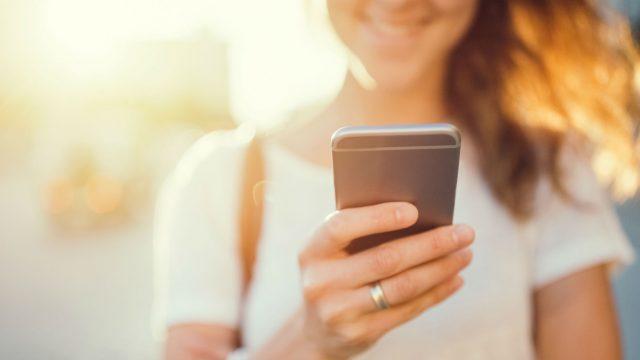 Junge Frau kontrolliert die Tiefenschärfe ihrer Smartphone-Bilder.