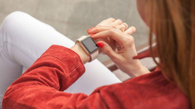 Junge Frau schaut auf ihr Apple-Watch-Display.