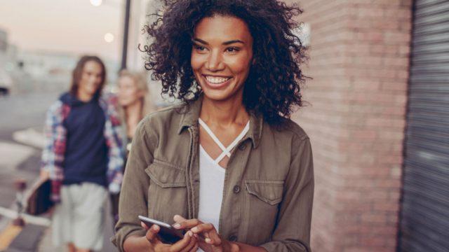 Junge Frau lächelt und macht einen Screenshot mit ihrem Smartphone.