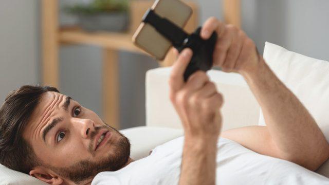 Junger Mann spielt Creative Destruction auf seinem Smartphone