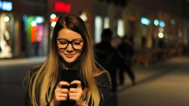 Junge Frau aktiviert am Smartphone den Dark Mode ihrer Android-App.