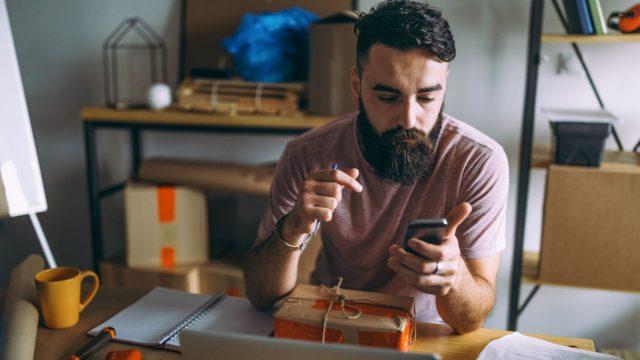 Junger Mann sitzt mit Smartphone an seinem Schreibtisch