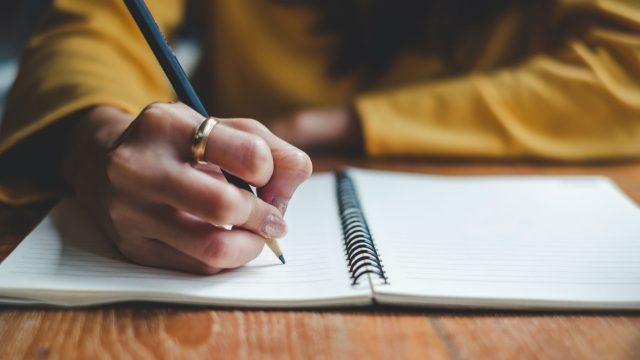 In ein Notizbuch schreiben.