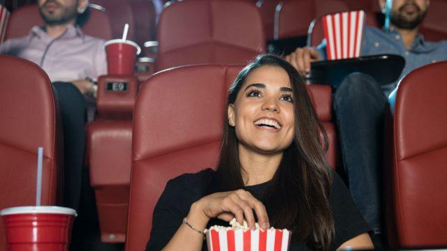 Junge Frau sieht sich einen Film im Kino an.