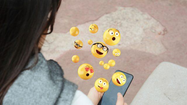 Junge Frau nutzt Emojis auf ihrem Smartphone.