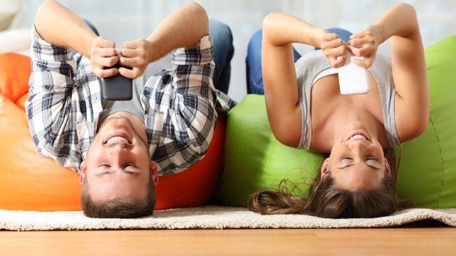 Junges Pärchen spielt Brettspiel-Apps gegeneinander