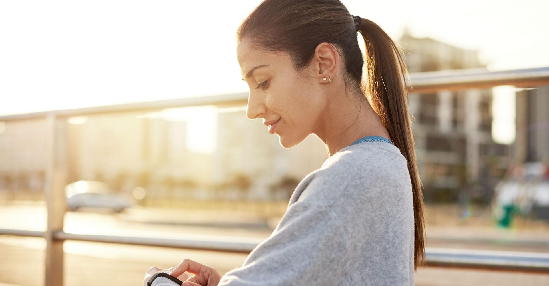 Junge Frau tippt auf das Display ihres Fitbit-Trackers.