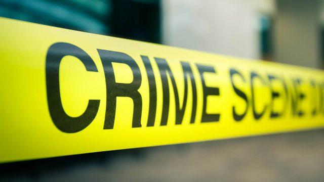 """Gelbes Absperrband mit der Aufschrift """"Crime Scene Do Not Cross""""."""