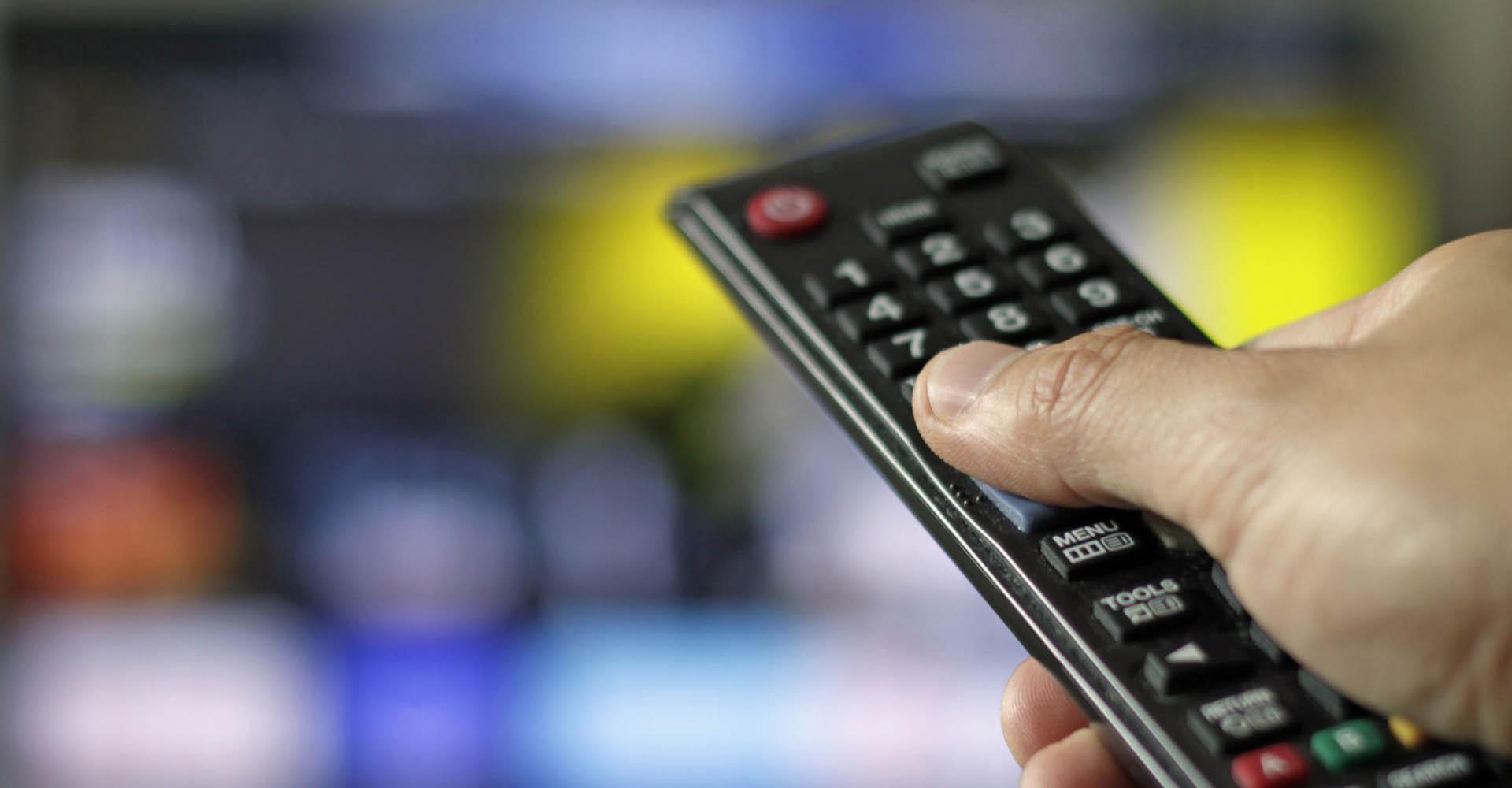 Mit der Fernbedienung das Fernsehgerät steuern.