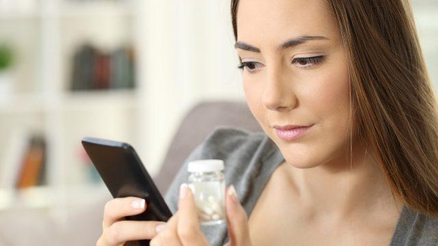 Eine Frau betrachtet Tabletten und ein Smartphone.