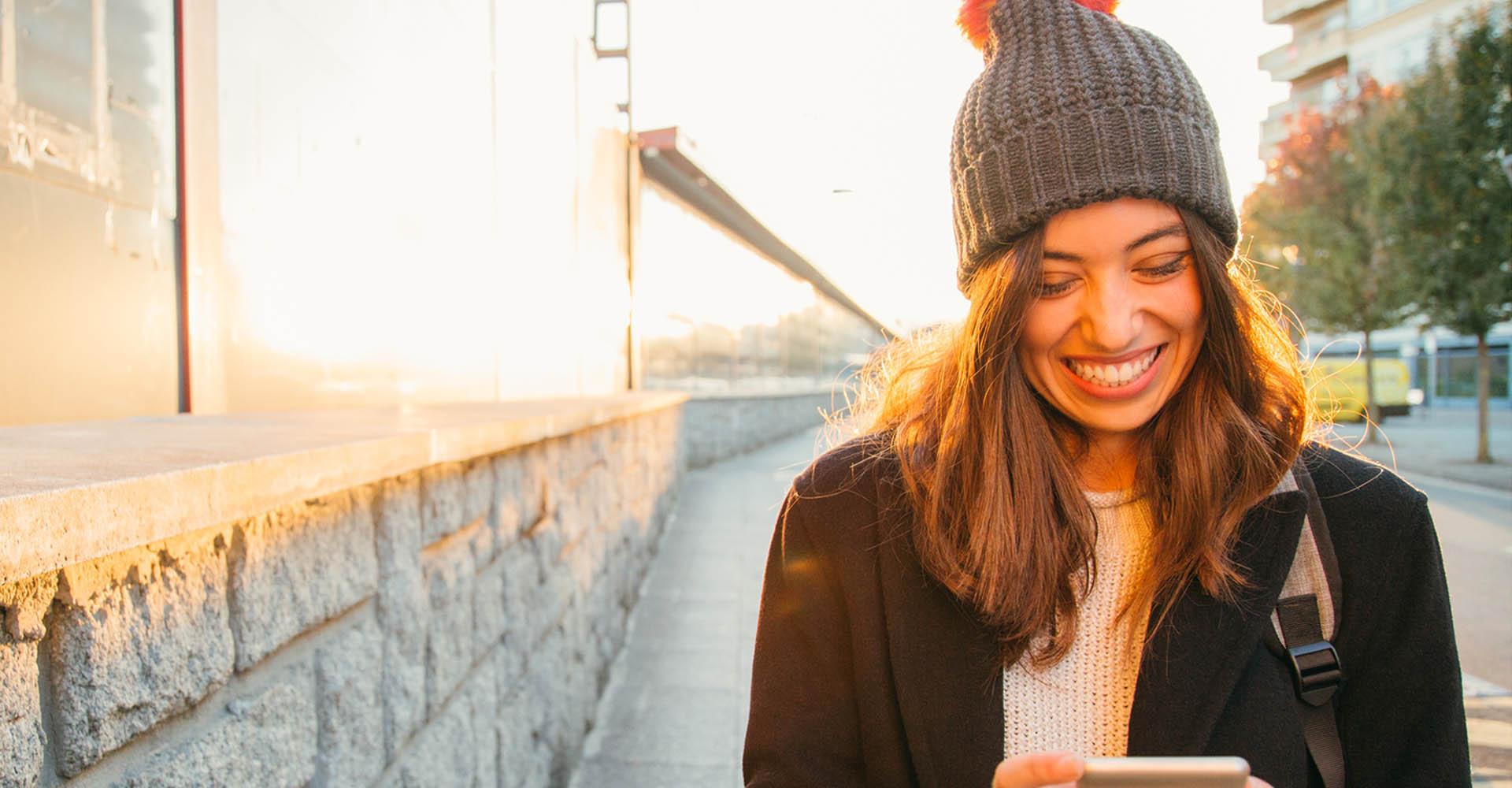 Junge Frau stellt am iPhone die Anrufaudioausgabe um.