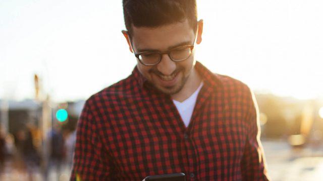 Junger Mann bearbeitet am iPhone die Anrufeinstellungen.
