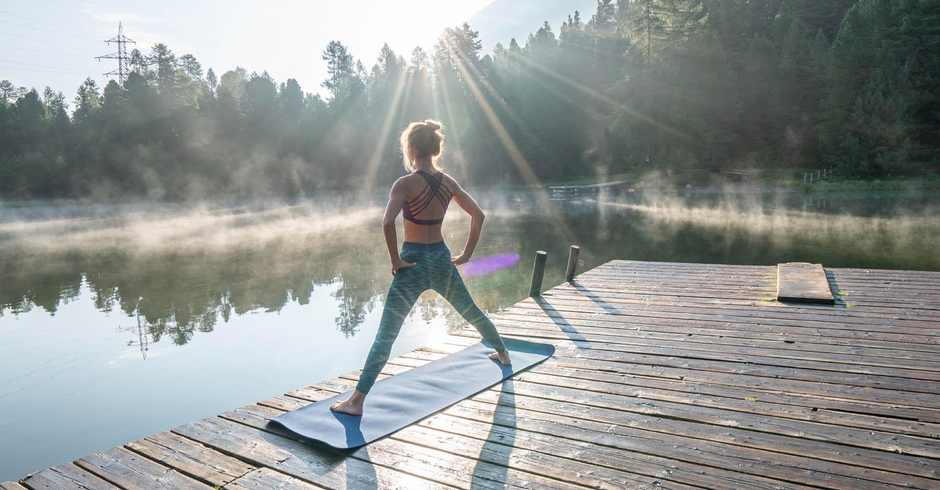 Eine Frau macht am Steg Yoga.