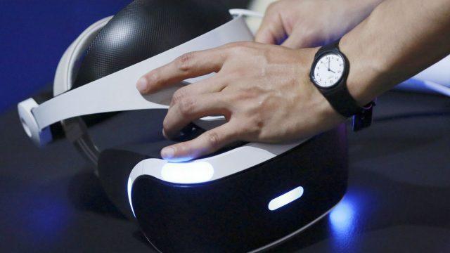 Die VR-Brille der PlayStation VR in die Hand nehmen.