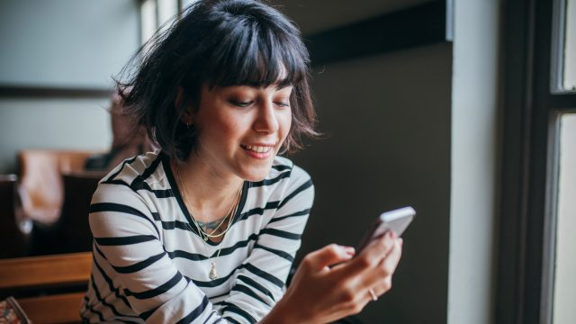 Frau nutzt Telegram auf Handy