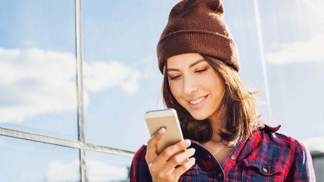 Junge Frau nutzt ein iPhone mit iOS 12.3.