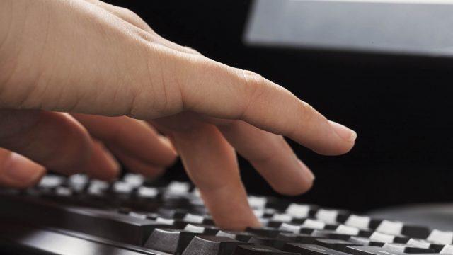 Menschliche Hand drückt Tasten auf der Tastatur.