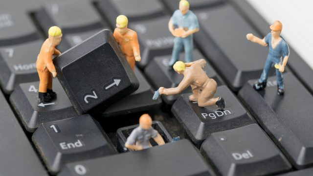Kleine Männchen reparieren eine defekte Tastatur