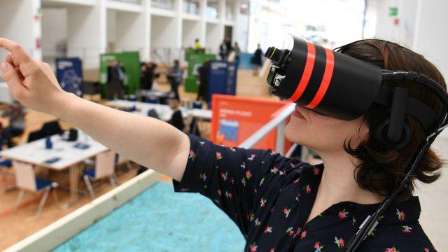 Eine Frau trägt eine VR-Brille und erlebt Inhalte in der virtuellen Realität.