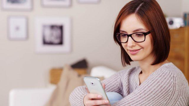 Frau probiert am Smartphone die neuen Telegram-Einstellungen aus.