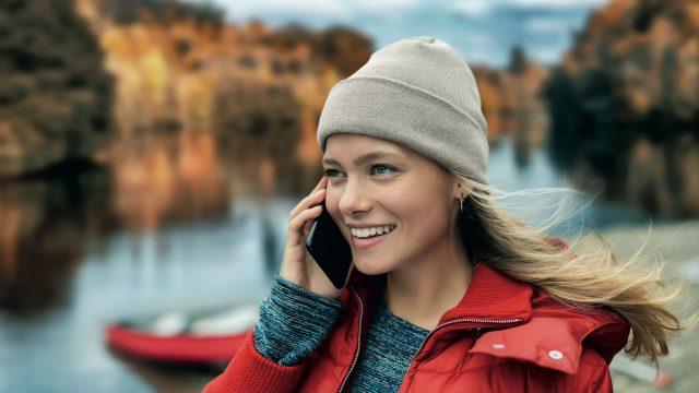Eine Frau steht an einem See mit Boot und telefoniert.