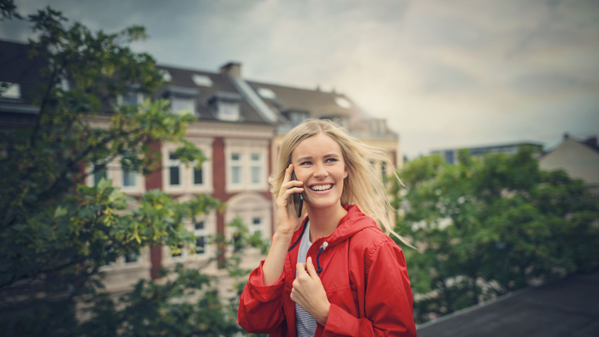 Eine Frau mit roter Jacke steht auf einem Dach und telefoniert lachend.