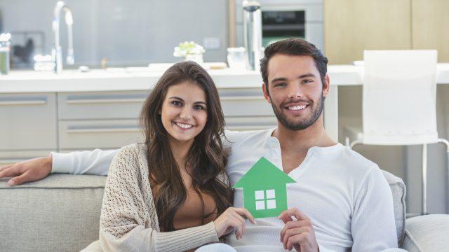 Paar hält kleines Haus in der Hand